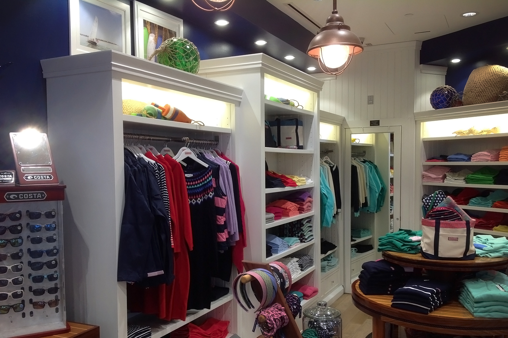 Wide view of white wall fixtures displaying apparel.