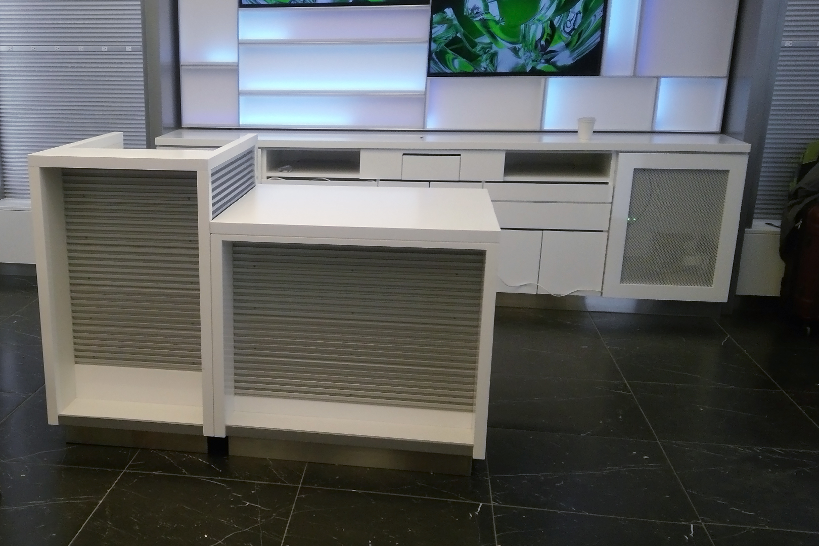 Tech on the go free standing slat wall fixture with backlit wall fixture in the background.